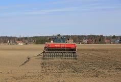 Traktor och Seeder på fält på våren Arkivbild