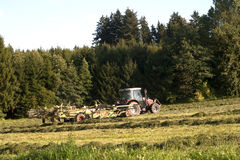 Traktor op het werk aangaande een gebied stock foto
