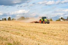 Traktor på fält Arkivfoto