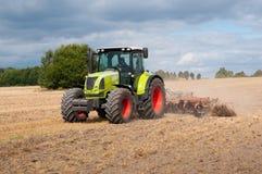 Traktor på fält Royaltyfria Bilder