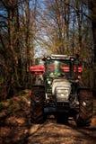 Traktor på stora hjul på jordvägen i vårskog Royaltyfria Foton