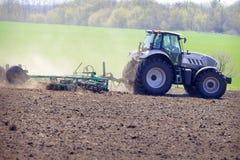 traktor på stora hjul på plöjt fält mot grönt fält Arkivbild