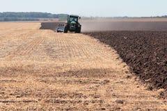 Traktor pflügt das Land Stockfotos