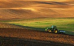 Traktor pflügt ein Feld im Frühjahr, das von Türme Traktor begleitet wird Stockfoto