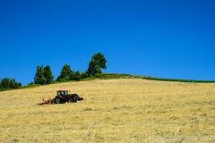 Traktor pflügt ein Feld im Sommer Lizenzfreie Stockfotos