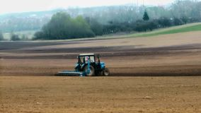 Traktor plows the land in spring. Fermer hopes for a good harvest in summer stock video footage