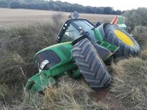 Traktor rullande över i skörden Arkivbild