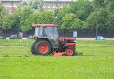 Traktor Russlands St Petersburg im Juli 2016 mäht das Gras Stockfotografie