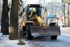 Traktor säubert die Straße in der Stadt des schmutzigen Schnees Stockbild