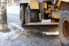 Traktor säubert die Straße in der Stadt des schmutzigen Schnees Stockfotografie