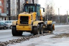 Traktor säubert die Straße in der Stadt des schmutzigen Schnees Lizenzfreies Stockfoto