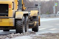 Traktor säubert die Straße in der Stadt des schmutzigen Schnees Stockbilder
