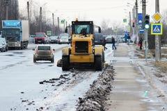 Traktor säubert die Straße in der Stadt des schmutzigen Schnees Lizenzfreie Stockfotos