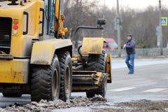 Traktor säubert die Straße in der Stadt des schmutzigen Schnees Lizenzfreie Stockfotografie