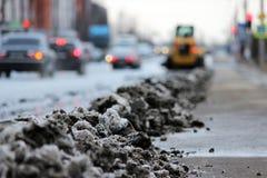 Traktor säubert die Straße in der Stadt des schmutzigen Schnees Lizenzfreie Stockbilder