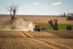 Traktor som arbetar i ett mellanvästern- fält Arkivfoto