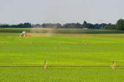 Traktor som arbetar på det jordbruks- fältet Arkivbild