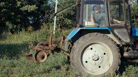 Traktor som arbetar på potatisfältet Plockningpotatisar med att använda traktoren royaltyfria bilder