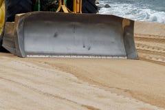 Traktor som arbetar på stranden Arkivfoto