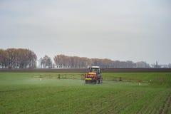 Traktor som besprutar bekämpningsmedel på stort grönt fält med ungt korn royaltyfri fotografi