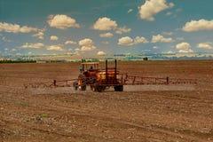 Traktor som besprutar bek?mpningsmedel arkivbilder