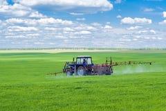 Traktor som besprutar ett lantgårdfält arkivfoto