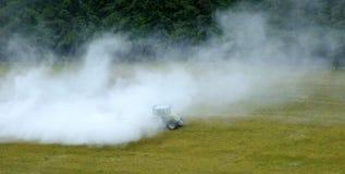 Traktor som besprutar fältet, i moln av pesticide/limefrukt arkivfoton