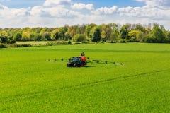 Traktor som besprutar glyphosatebekämpningsmedel på ett fält Arkivbilder