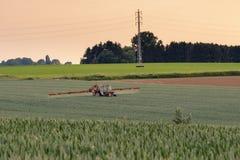 Traktor som besprutar gröna skördar Fotografering för Bildbyråer