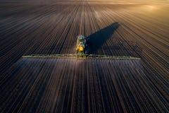 Traktor som besprutar jord i fält royaltyfri bild