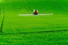 Traktor som besprutar kemikalieerna Arkivfoto