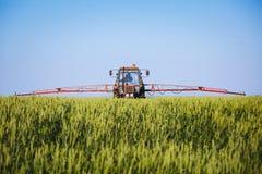 Traktor som besprutar vetefältet med sprejaren Royaltyfri Fotografi