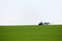 Traktor som besprutar vetefältet med sprejaren i vår Arkivfoton