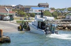 Traktor som drar släpet och dykfartyget från havet Arkivbild