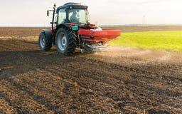 Traktor som fördelar konstgjorda gödningsmedel Arkivbild