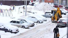 Traktor som gör ren snöig dag för insnöad vinter i stad Tjänste- medel för vinter i arbete Medel för snöborttagning lager videofilmer