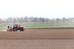 Traktor som harvar fältet Royaltyfri Bild