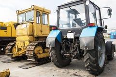 Traktor som i rad står Parkering av jordbruks- maskineri Arkivfoto