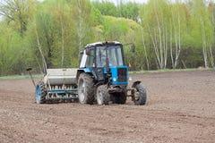 Traktor som kärnar ur fältet Royaltyfria Bilder