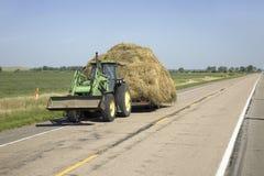 Traktor som ner drar hö Arkivbild