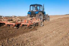 Traktor som odlar jord Royaltyfria Bilder