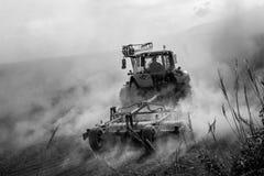 Traktor som plogar en dammig fältblach och vit royaltyfri foto