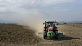 Traktor som plogar ett dammigt fält i delta arkivfoto