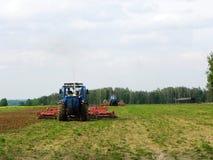 Traktor som plogar fältet, innan att plantera för vår Närbild landskap royaltyfria foton