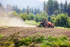 Traktor som plogar för att så den gula potatisen Fotografering för Bildbyråer