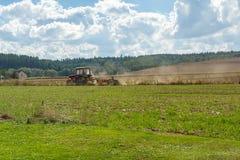 Traktor som plogar i fält Fotografering för Bildbyråer