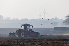 Traktor som plogar landet i morgonen arkivfoto