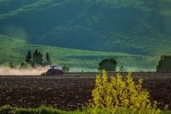 Traktor som plogar torrt land royaltyfria foton