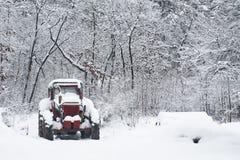 Traktor som täckas av snow Arkivbilder
