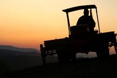 Traktor am Sonnenuntergang Lizenzfreie Stockbilder